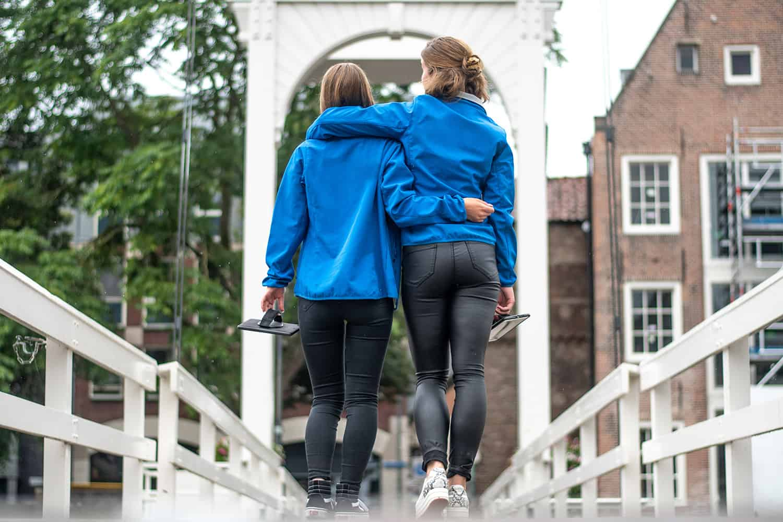 meisjes lopen arm in arm over een brug